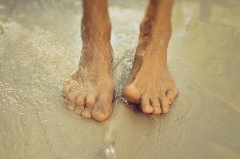 Pés na água do mar em praia